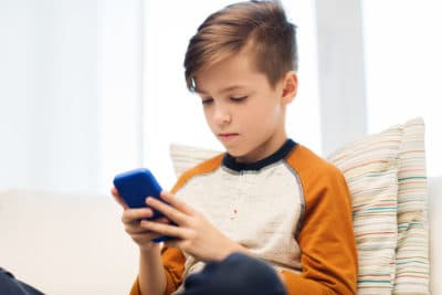 Boy playing game on smart phone