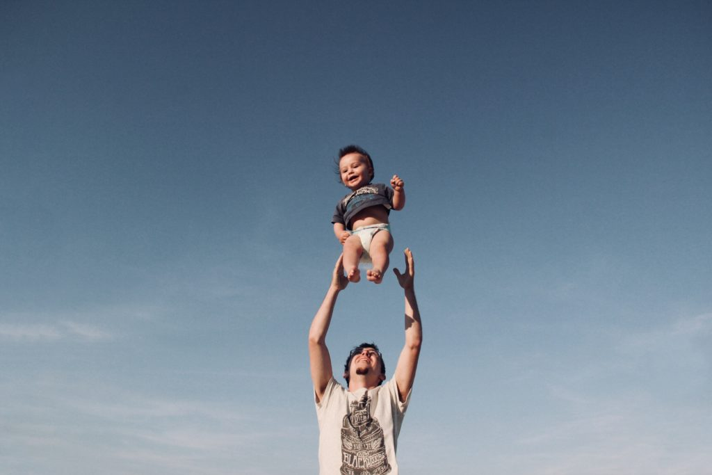 dad tossing baby into blue sky