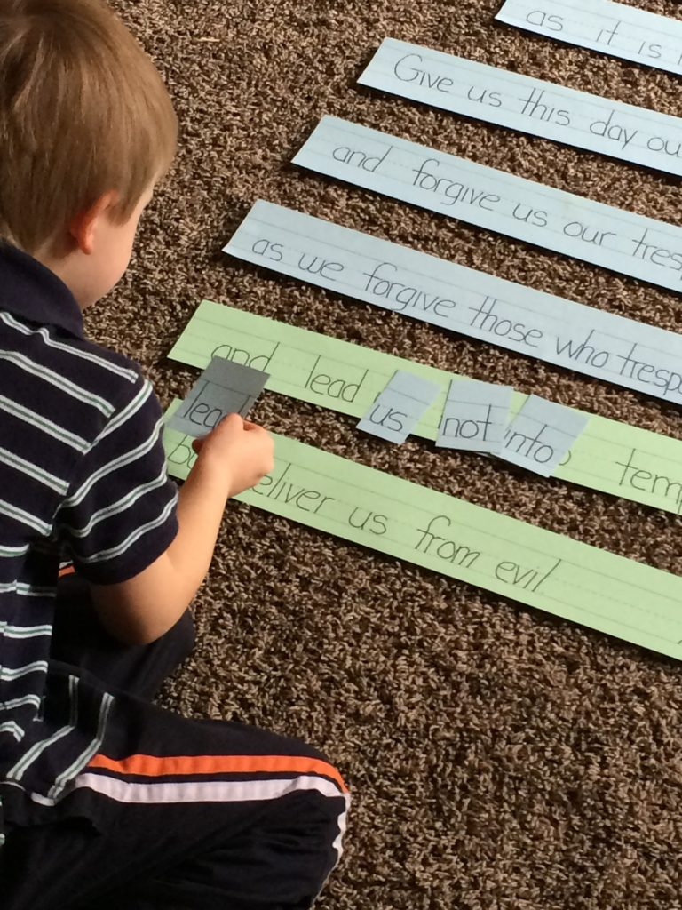 Boy placing word cards on printed sentences