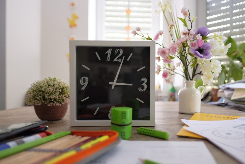 Clock and school supplies on desk