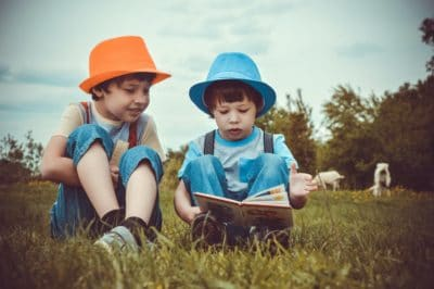 2 boys sitting on green grass looking at a book