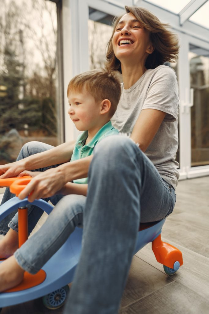 mom with preschool son on ride on toy