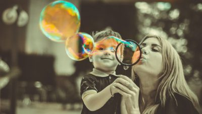 mom and son blowing bubbles together outside