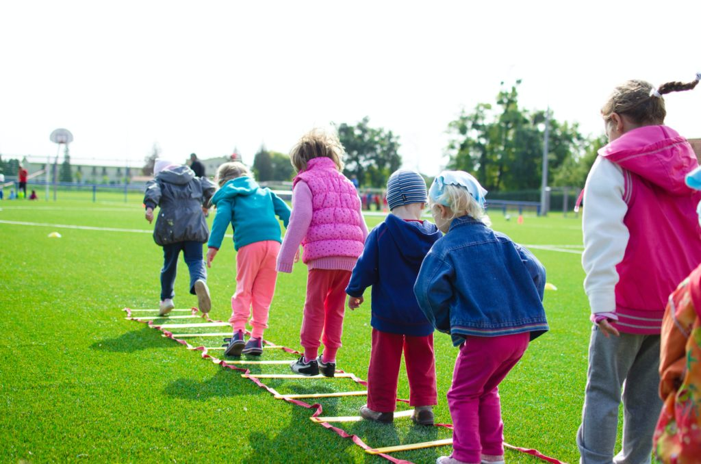Kids lined up and standing in rings on a grassy field