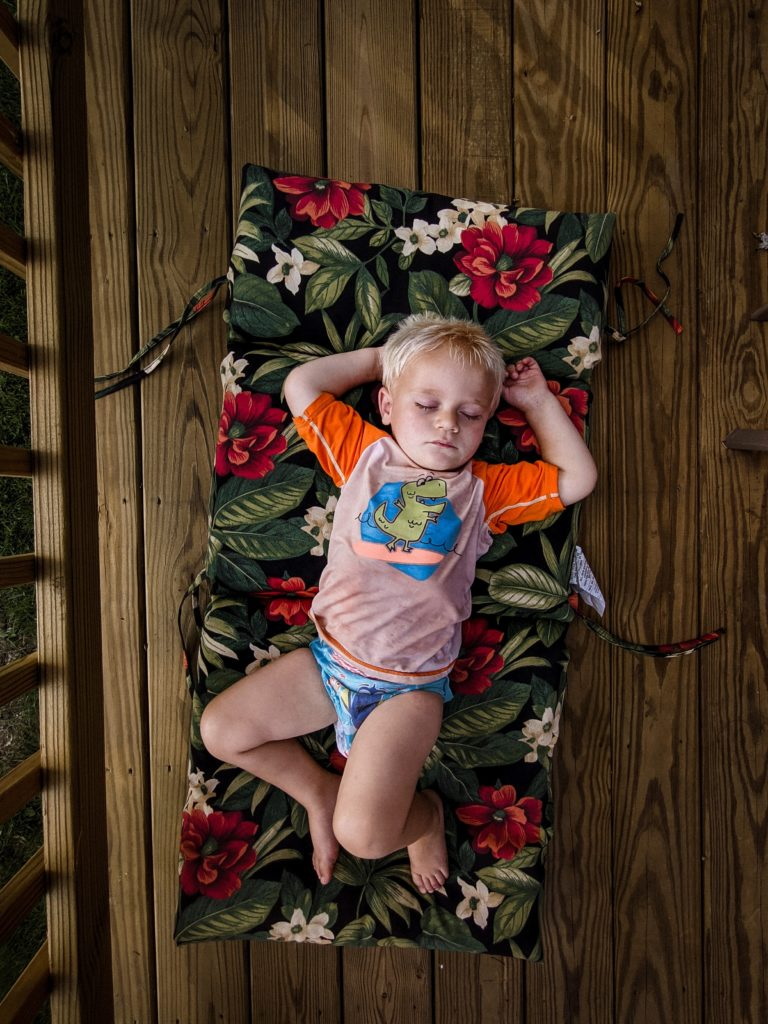 Blond boy laying on a mat, sleeping