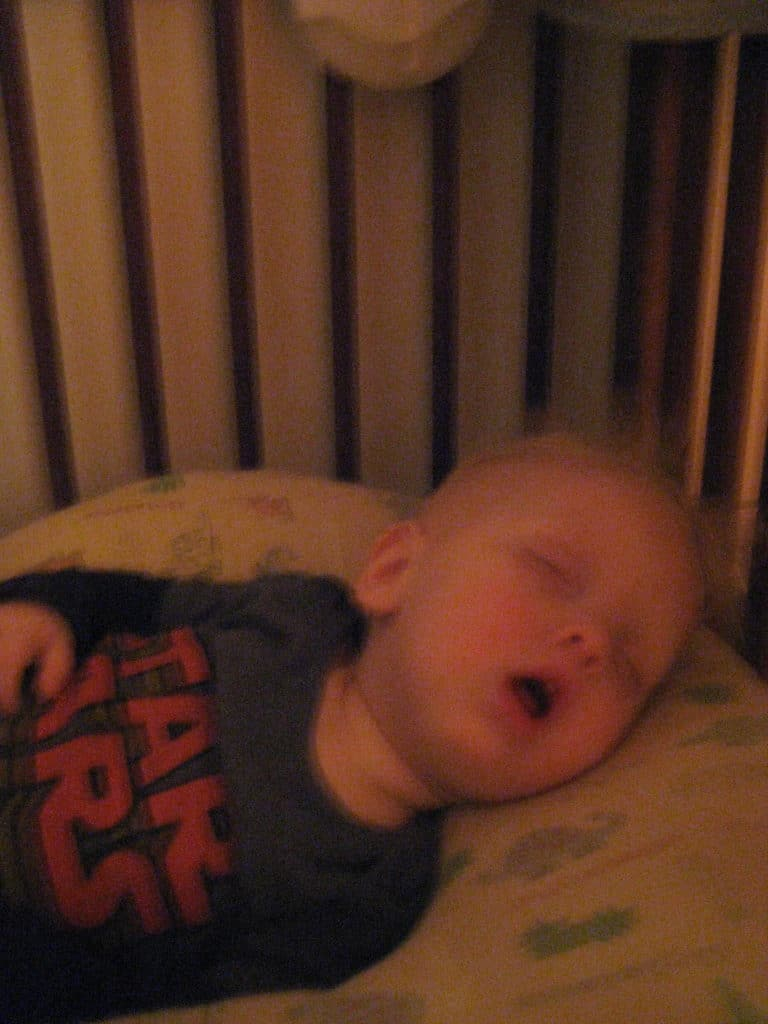 blond boy snoring with mouth open in crib