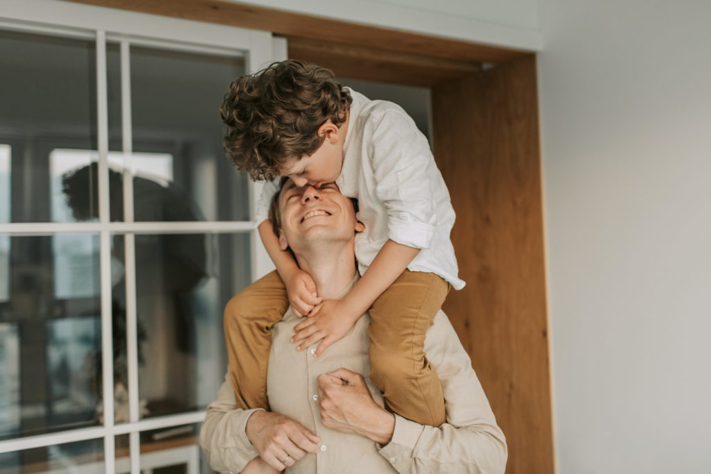 man carrying son on his shoulders