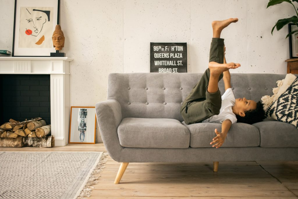 Young black boy laying on his back on couch, legs in air